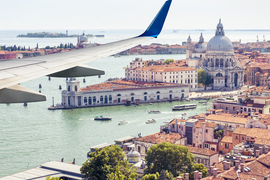 Plane flies above Venice, Italy. View of city from airplane window. Concept of flight, vacation and summer air travel.