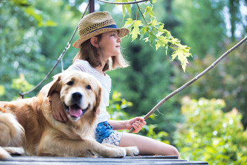 Young girl fishing while sitting with dog on pier
