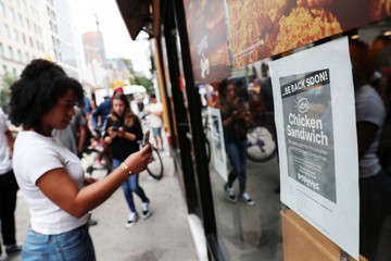 A woman takes a picture of a sign posted outside Popeyes Louisiana Kitchen stating that the restaurant is out of their new chicken sandwiches in New York