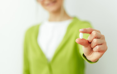 Close-up image of a pill in hand with blurred view of smiling woman. Beautiful young woman wearing green cardigan and white t-shirt taking pill isolated on white wall. Vitamin, dietary Supplements.