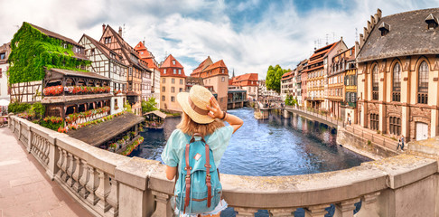 Young girl with backpack standing on a bridge over d Ill river in Strasbourg, France Wall mural