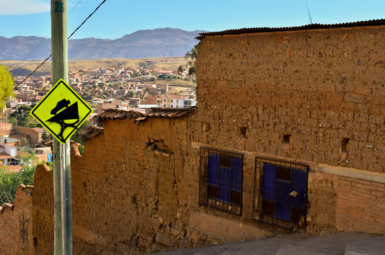 Street downhill with red brick facades and a traffic sign, in Sucre, Bolivia