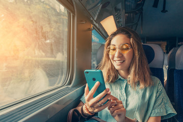 Happy Asian girl using transport application on smartphone while travelling by high speed train