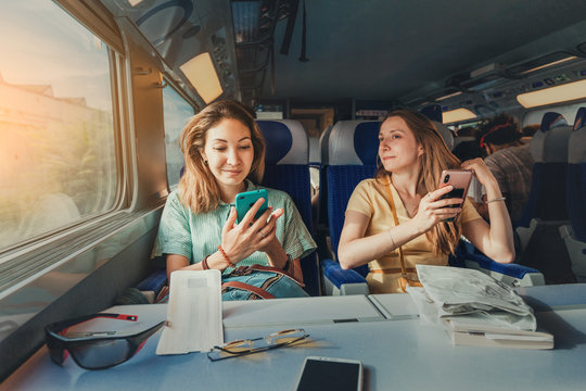 Happy two female friends travelling by long distant high speed train using their smartphones