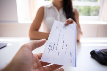 Businesswoman Giving Cheque To Colleague