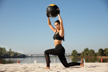 Young healthy woman doing lunges with ball at the beach. Single caucasian female model training air at the river side in sunny day. Concept of healthy lifestyle, sport, fitness, bodybuilding.