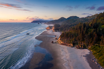 Aerial View of Arch Cape, Oregon. Sunset along the Oregon coast near Cannon Beach features white sand beaches with fir and cedar forests as far as the eye can see.
