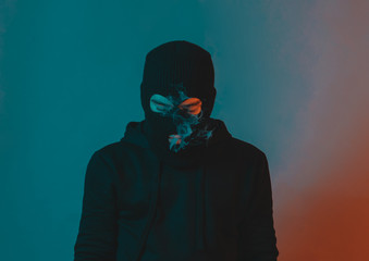 young man in hoodie and balaclava looking down and blow smoke out - fototapety na wymiar