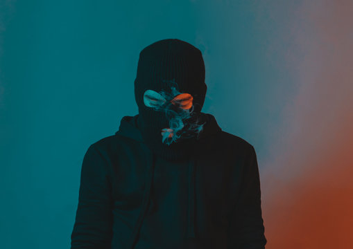 young man in hoodie and balaclava looking down and blow smoke out
