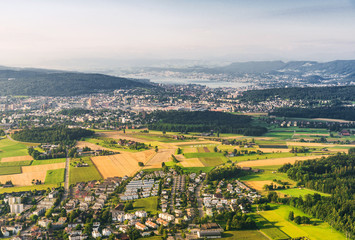 Landscape aerial view of Zurich city, Switzerland, with colorful houses, forest with trees, lake Zurich, hills, and fields