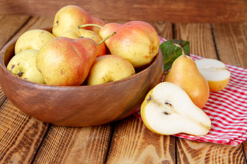 Autumn still life. Pears on old wooden table with red checkered tablecloth. Rustic design.