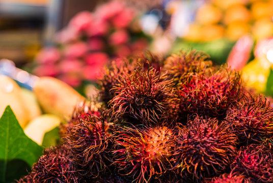 Close up food photo of organic rambutan exotic fruit at the farmers market stall