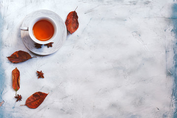 A cup of hot tea with fall leaves and copy space