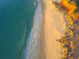 Scenic vertical aerial view of beautiful turquoise ocean surf, pristine remote beach and orange colored rocks and sand dunes at sunset as background and copy space.