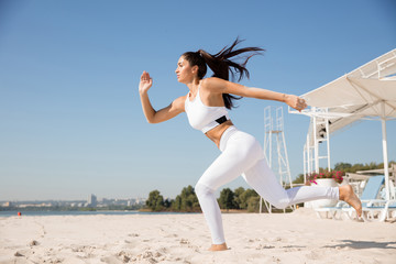 Young healthy woman running and doing lunges at the beach. Single caucasian female model practicing at the river side in sunny day. Concept of healthy lifestyle, sport, fitness, bodybuilding.