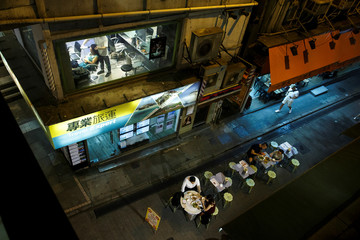 People eat at street food stall and a woman sits in a hair salon in the Central business district in Hong Kong
