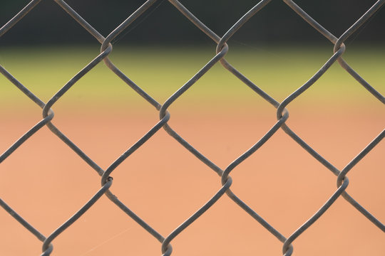 Close up picture of chain link fence with blurred baseball field in background.