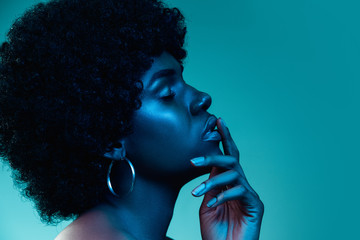 Deep ocean. Portrait of female fashion model in neon light on blue gradient studio background. Beautiful african woman with trendy make-up and well-kept skin. Vivid style, beauty, cosmetics concept. Fotoväggar