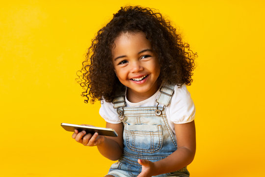 Cute african american girl holding cellphone and smiling