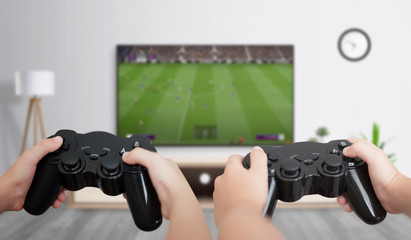 Boys play soccer on the gaming console on a large TV in the room. The concept of fun and gaming for friends.