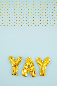 Inflated letters yay ove the pastel background with golden polka dots. Party, celebration, holidays