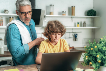 Father standing near son with laptop computer