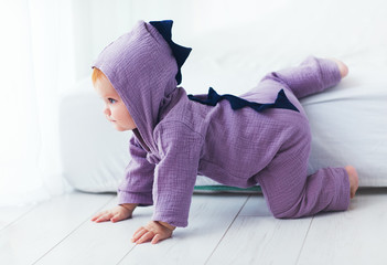 funny, nine month old, infant baby girl in dinosaur costume, going down from the bed