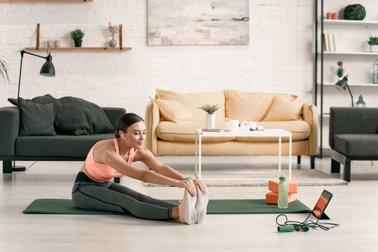 Cheerful woman stretching while using touchpad stock photo