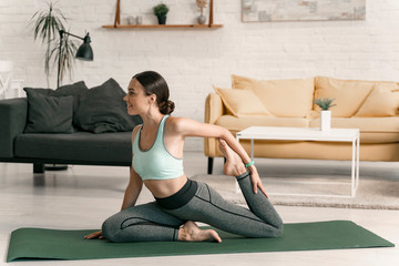Smiling female stretching legs indoors stock photo
