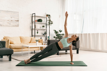 Merry woman balancing in side plank stock photo
