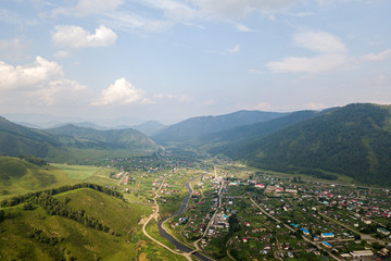 Picturesque landscapes of ALtai, Siberia: view of village and mountains.High rocks, amazing sky at sunset in summer.  Travel background. ..