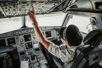 Adult pilot looking at control panel in cabin