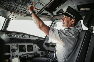 Fototapeta Concentrated pilot in cockpit looking at control panel obraz