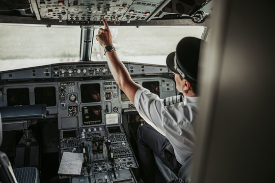 Mature pilot in cockpit looking at control panel