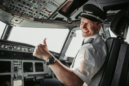 Smiling pilot in cockpit looking at camera