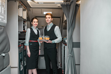 Smiling flight attendant with pilot posing for camera