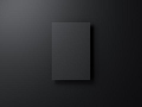 Black poster mockup hanging on black wall