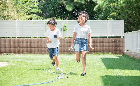 庭で水遊びをする子供