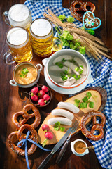 Bavarian sausages with pretzels, sweet mustard and beer mugs