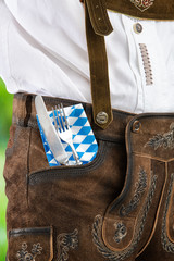 Man in traditional Bavarian Lederhosen with cutlery