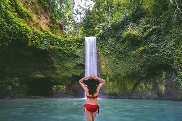 Wall Mural - Woman standing in Tibumana waterfall in Bali island, Indonesia.