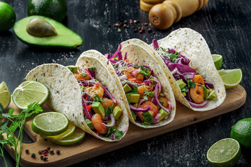 Delicious tacos with shrimps, avocado, onion and lime on a wooden board. Classic Tex-Mex cuisine meal.