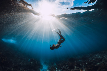 Free diver woman with fins over coral bottom and amazing sun rays.