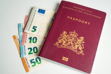 Dutch passport with Euros next to it. Five, ten, twenty and fifty Euros