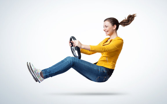 Young happy smiling girl drives a car with steering wheel in hands, auto concept