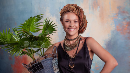 Southern flavor. A young tanned woman with afro braids smiles holding a big pot with a tropical plant.