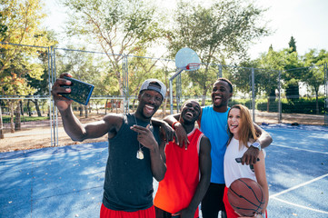 Four friends take picture with mobile phone in basketball court