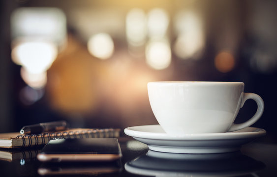 Closeup white cup of coffee with smartphone, notebook and pen on table in cafe. Vintage light, blurred and bokeh background