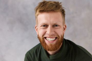 Sincere human emotions, feeings and reaction. Studio image of good looking charismatic young man with earrings and thick beard laughing at joke, being in good mood, smiling broadly, showing his teeth