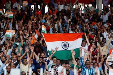 Indian crowd wave their flags as they wait for Indian Prime Minister Narendra Modi at a community gathering during his two-day visit, at Bahrain National Stadium, Isa Town, in Manama